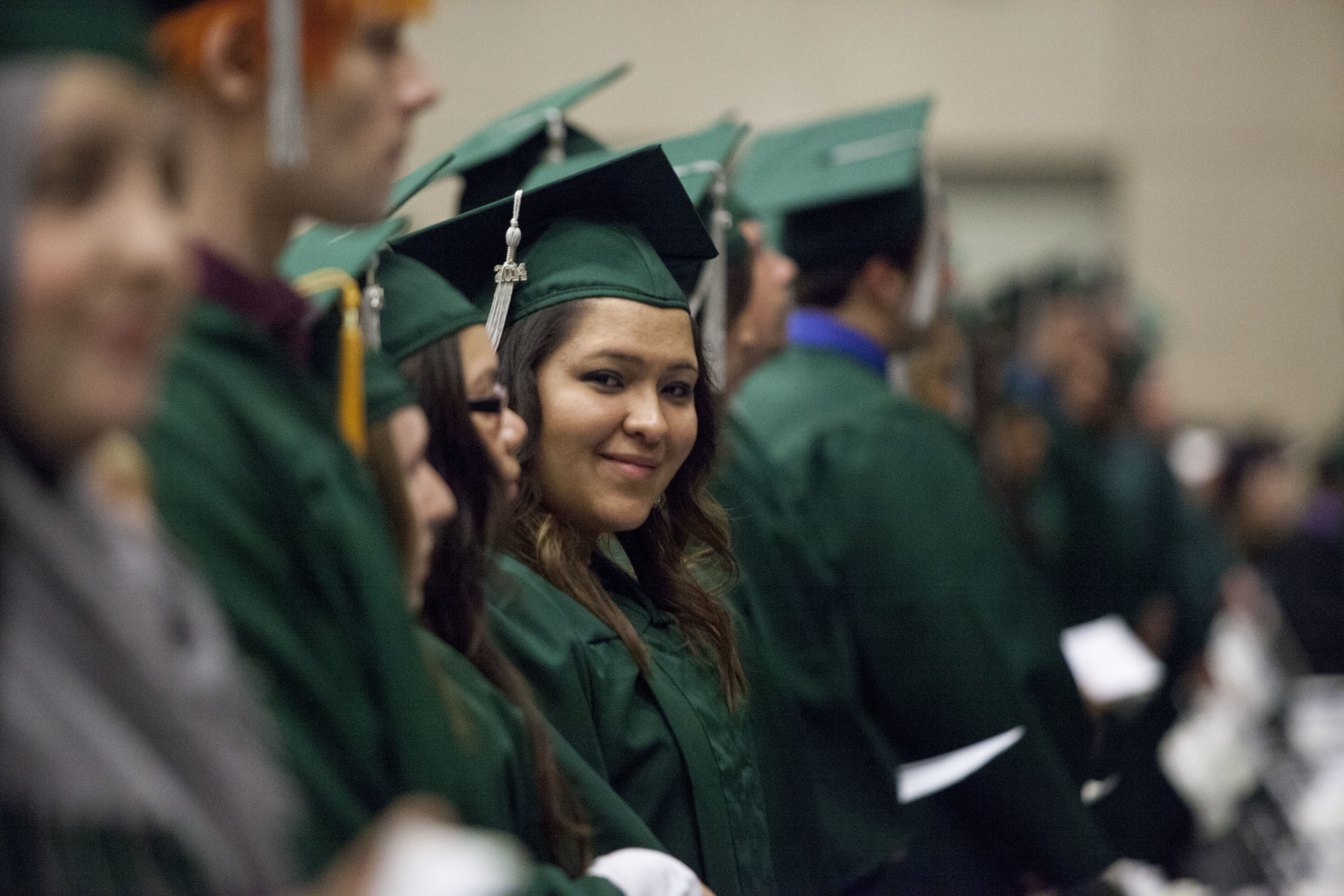 Girl in green cap & gown - ideas42